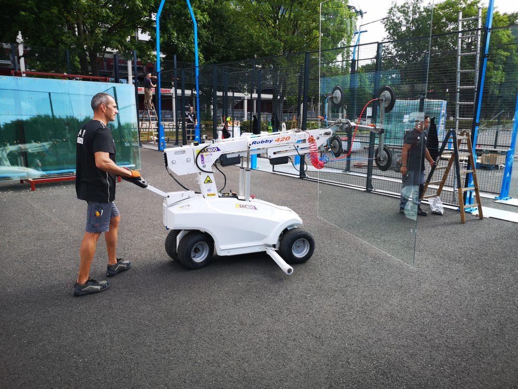 Mehrere Männer bauen einen Padel Court mit Hilfe von schwerem Gerät am Rheinenergie Stadion in Köln auf